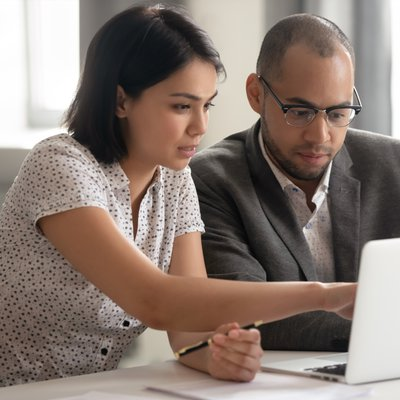 Generic image of a woman and a man, sat together, looking at work on a laptop screen