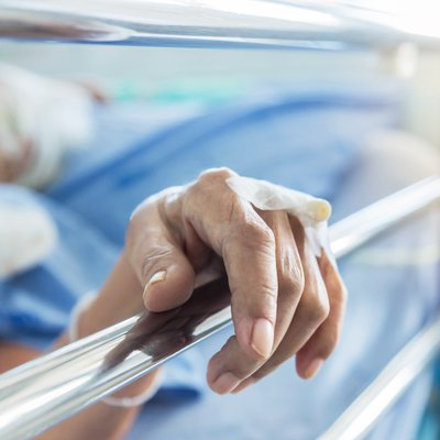 Image of patient hand in hospital bed