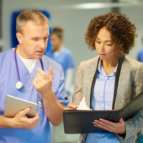 A doctor and investigator discussing a file in a hospital corridor.