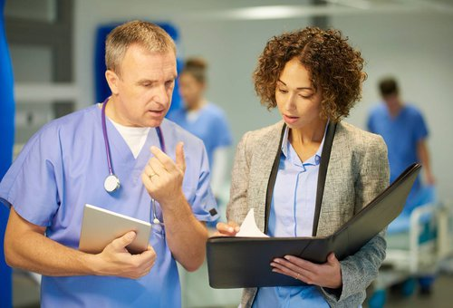 Two doctors discussing results on a clipboard.