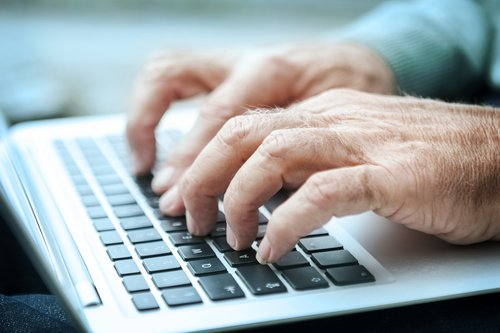 An older person uses a computer